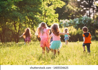 Large group of kids, friends boys and girls running in the park on sunny summer day in casual clothes  - Shutterstock ID 1405534625