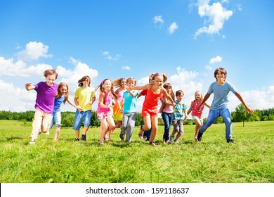 Large group of kids, friends boys and girls running in the park on sunny summer day in casual clothes