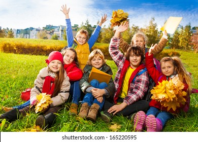 Large group of kids, friends, boys and girls around 10 years old, sitting in the grass in autumn clothes with maple leaves bouquets and papers after school with lifted hands