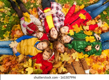Large group of kids laying in the grass with maple leaves all over them on autumn day