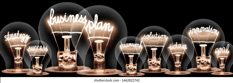 Large group of light bulbs with shining fibers in a shape of Business Plan, Strategy, Innovation and Success concept related words isolated on black background