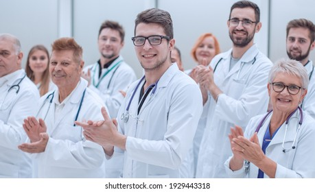 large group of medical practitioners applauding together.