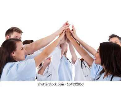Large group of motivated doctors and nurses standing in a circle giving a high fives gesture with their hands meeting in the centre  conceptual of teamwork isolated on white