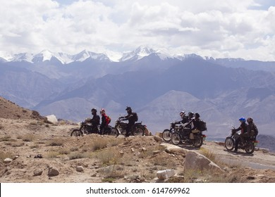 A large group of Motorcyclists on a mountainous road, cold overcast weather. Extreme sport, active lifestyle, adventure touring concept. High mountains, dirt roads.