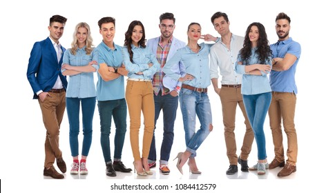 large group of nine happy casual men and women standing on a white background