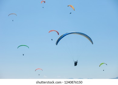 A large group of paragliders enjoy a thermal updraft in the Nepal Himalayas