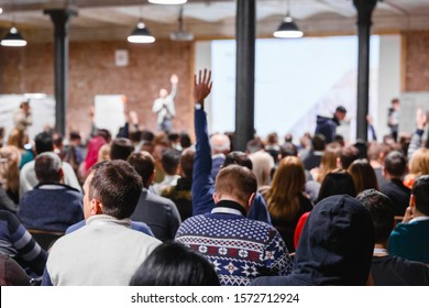 Large group of people at the Conference Watching Presentation and listening to speaker. Business people concept and Ideas, education. Speaker interacting to listener from auditorium, raising hang.