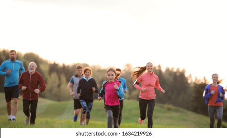 A large group of people cross country running in nature.