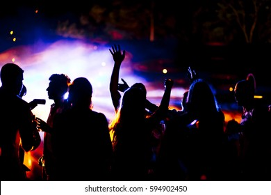 Large group of people on a dance floor. There is a very vivd colorful backlight.