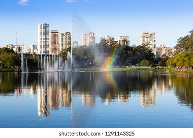 A large group of people watching the rainbow formed by the drops of the fountain of the Ibirapuera Park and in the background the luxury residential buildings, Sao Paulo, Brazil.