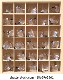 large group shot of multiple many organised safety glasses googles on a shelf rack in a science laboratory or factory, school, workplace environment. WHS. OHS. Workplace safety symbols objects.