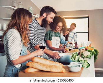 Large group of six friends preparing food for a cooking class at table at home or in a small culinary school