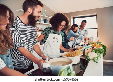 Large group of six happy friends preparing food for a pasta cooking class at table at home or in a small culinary school