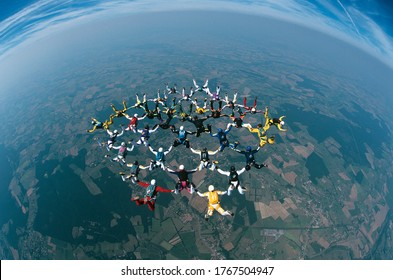 Large group of skydivers flying in formation over earth elevated view