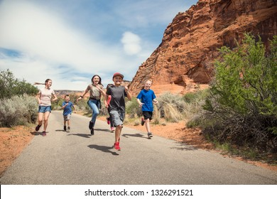 A large group of smiling kids running together on a pathway at a national park. Having fun out in nature during a summer vacation. Active, happy boys and girls