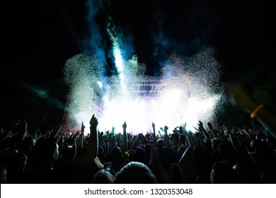 Large group of spectators watching confetti fireworks during live performance on music concert at night.