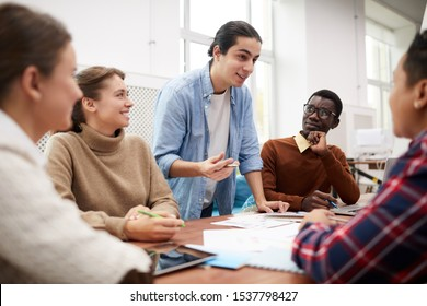Large group of students working together on team project while studying in college, focus on Lat-American man heading meeting
