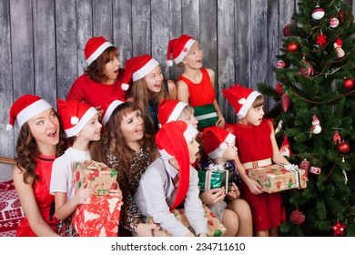 Large Group of surprised people in santa cluas hats holding presents and looking at Christmas tree