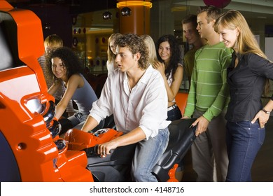 Large group of teenagers in amusement arcade. One teenage boy and girl sitting on motorcycles. Rest of people are standing behind them and smiling