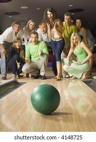 Large group of teenagers standing and crouching in bowling alley with hopeless faces. Looking at rolling ball