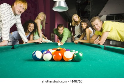 Large group of teenagers standing at pool table. Smiling and looking at camera. One person is playing billard