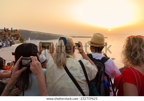 Large group of tourist watching and taking photos of famous sunset view in Oia village on Santorini island in Greece, Mediterranean Europe.
