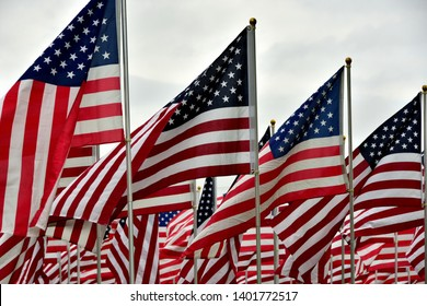 A large group of US Flags waving in honor for Memorial Day with multiple flags filling the background.