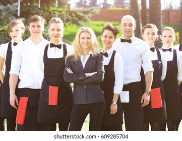 A large group of waiters and waitresses in the open air stand one after another