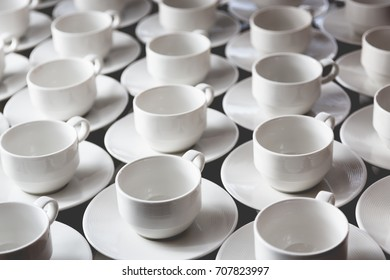 Large group of white coffee tea cups arranged in rows for self service. Horizontal full frame crop