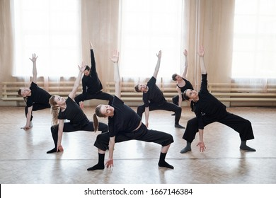 Large group of young fit people in black activewear exercising together during training on the floor of dance studio