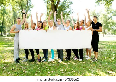 large group of young people holding a big white board