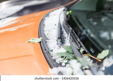 Large hail ice balls on car hood after heavy summer storm