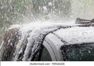 Large hail stones pelting car roof during storm