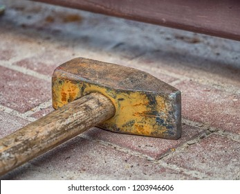 A large hammer lies on the paved ground