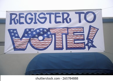 Large hand painted sign reads Register to Vote