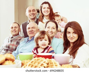 large happy family having tea and baked at home