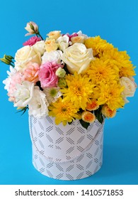 large hat box close-up on a blue background with fresh flowers: yellow chrysanthemums, white eustoma, pink eustoma, yellow roses, greens with blurred background