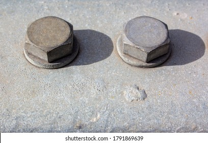 Large head bolts on metal construction as background - engineering concept. Metal heads of two bolts mounted on a metal surface. Hard shadow from the bolt heads. Close up of bolts holding plates.