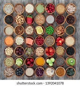 Large healthy super food collection in wooden bowls on rustic wood. High in antioxidants, anthocyanins, protein, smart carbs, vitamins and dietary fibre. Flat lay.