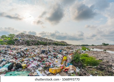 The large heap garbage dump extends parallel to the river,Garbage mountains with cloudy sky back ground in day light,Waste has petroleum products are the major.