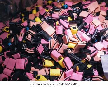 Large heap of liquorice licorice allsorts rainbow pink black yellow blue