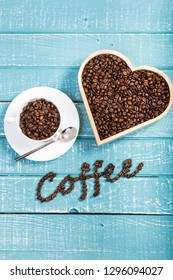 A large heart and cup filled with coffee beans on a weathered table with the word coffee