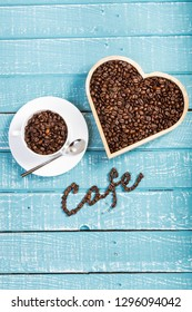 A large heart and cup filled with coffee beans on a weathered table with the word cafe