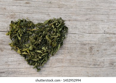 Large Heart Of Dried Cannabis Leaf Or Marijuana On Rustic Wooden Table Surface. Rasta Background.