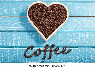 A large heart filled with coffee beans on a weathered table with the word coffee