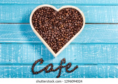 A large heart filled with coffee beans on a weathered table with the word cafe