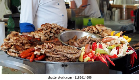Large heated tray with the traditional serbian street food. The typical grilled meats. like cevapi, sausages, pljeskavica and chicken, together with vegetables