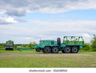 Large heavy duty industrial trucks with set of eight wheels and missle carrier trailer in camouflage color