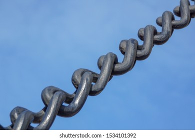 Large and heavy iron anchor chain against a blue sky.