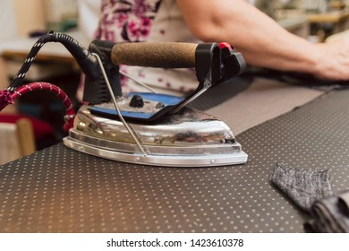 large, heavy, metallic iron in dry cleaning. woman ironing cloth for tailoring. production of clothes on an industrial scale